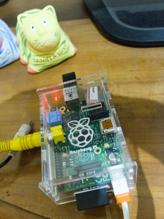 My Raspberry Pi Rev B, with 8GB SD Card, connected via RCA to my TV, controlled using a wireless keyboard. Yes, that's a clay cat.